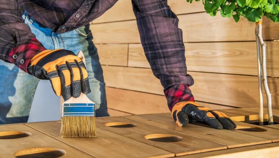 Applying polyurethane oil-based coating on outdoor wood.