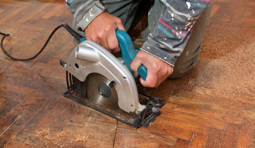 Worker is using circular saw blade to cut the hardwood floor.
