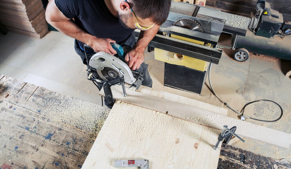 Woodworker sawing narrow board edge carefully with circular saw.