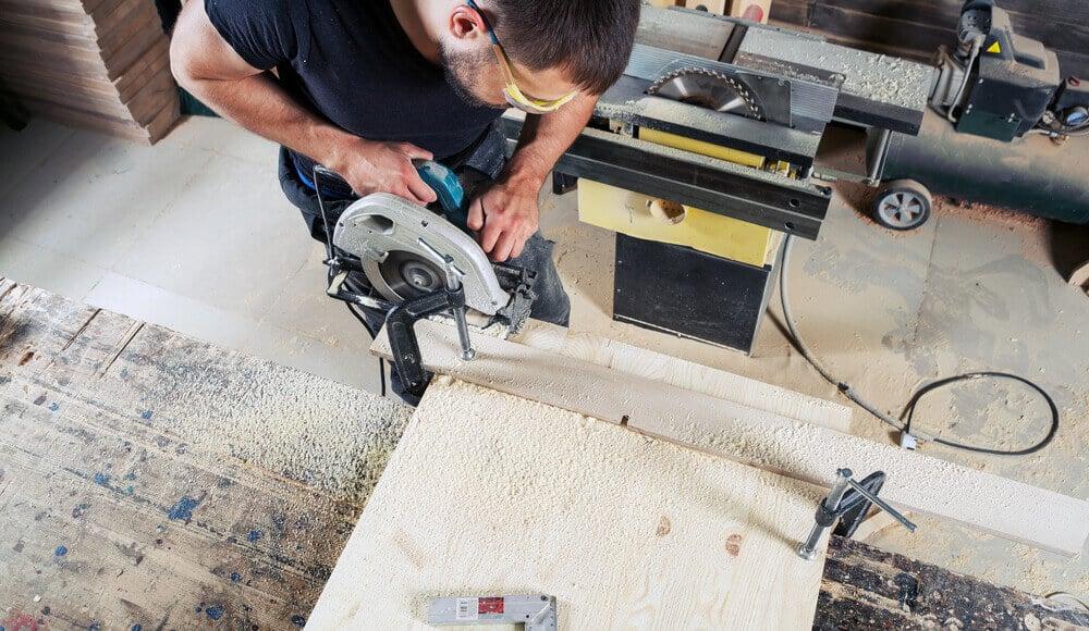 Woodworker sawing narrow board edge carefully with circular saw.