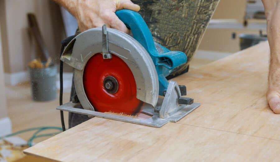 Worker cutting thin plywood board using circular saw.