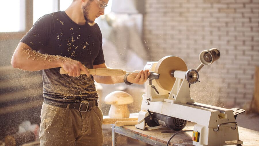 Beginner woodworker learn how to use basic wood lathe in workshop.