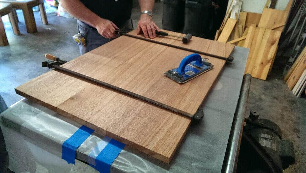 Arrange, glueing and clamping the wood planks for making tabletop.