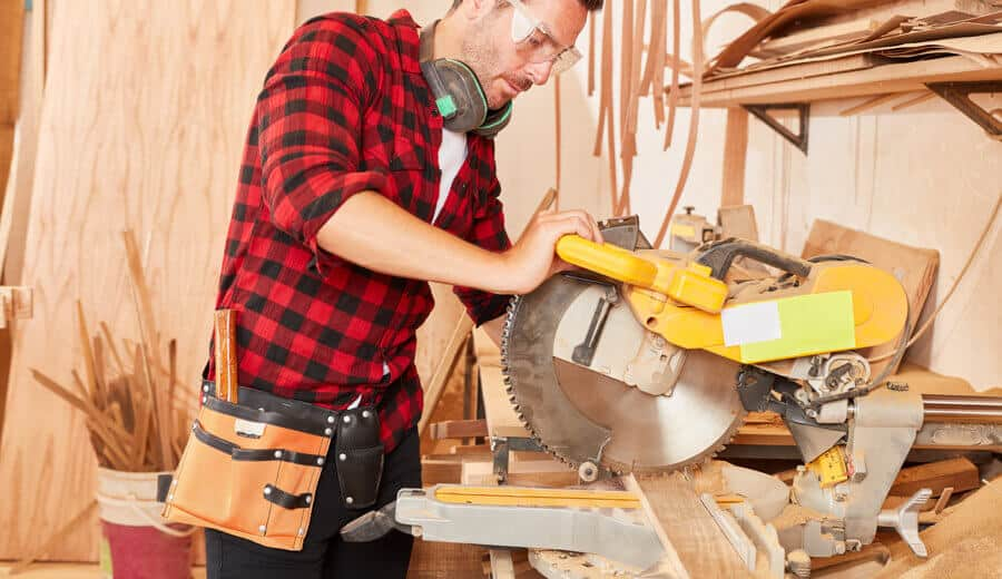 Woodworker cutting wood on the miter saw bench.