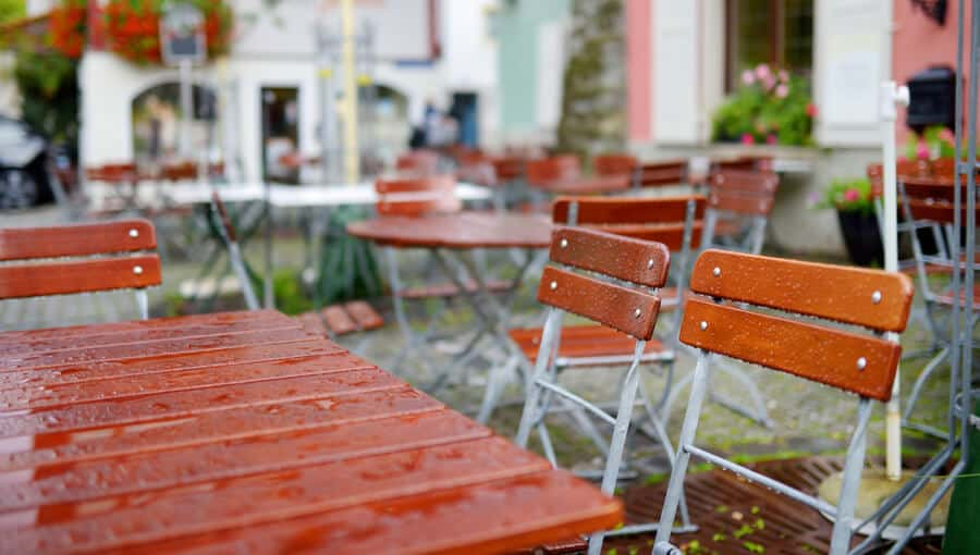 Waterproofed wood tables and chairs exposed to rain.