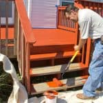 Home owner staining and painting deck with roller.