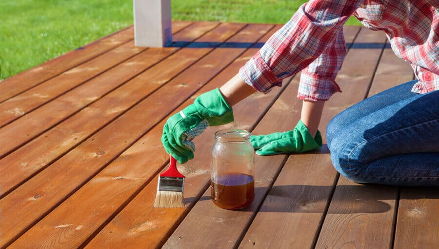 Applying new layer of oil-based stain on deck.