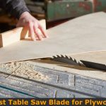 Cutting plywood sheet with table saw blade.