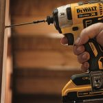 Using impact driver to drive screw into wood.
